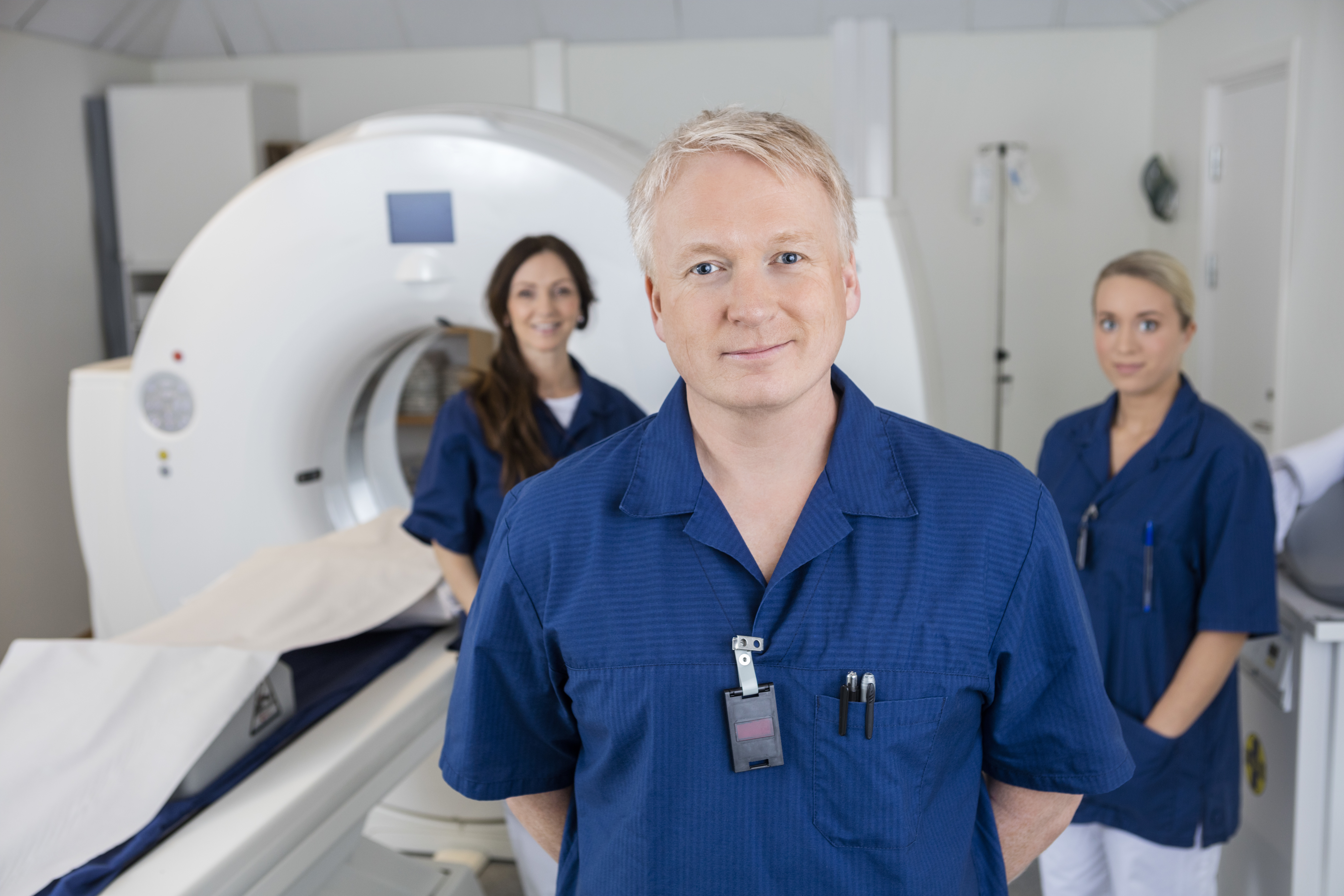 Portrait of confident male radiologist with colleagues standing by MRI machine in hospital