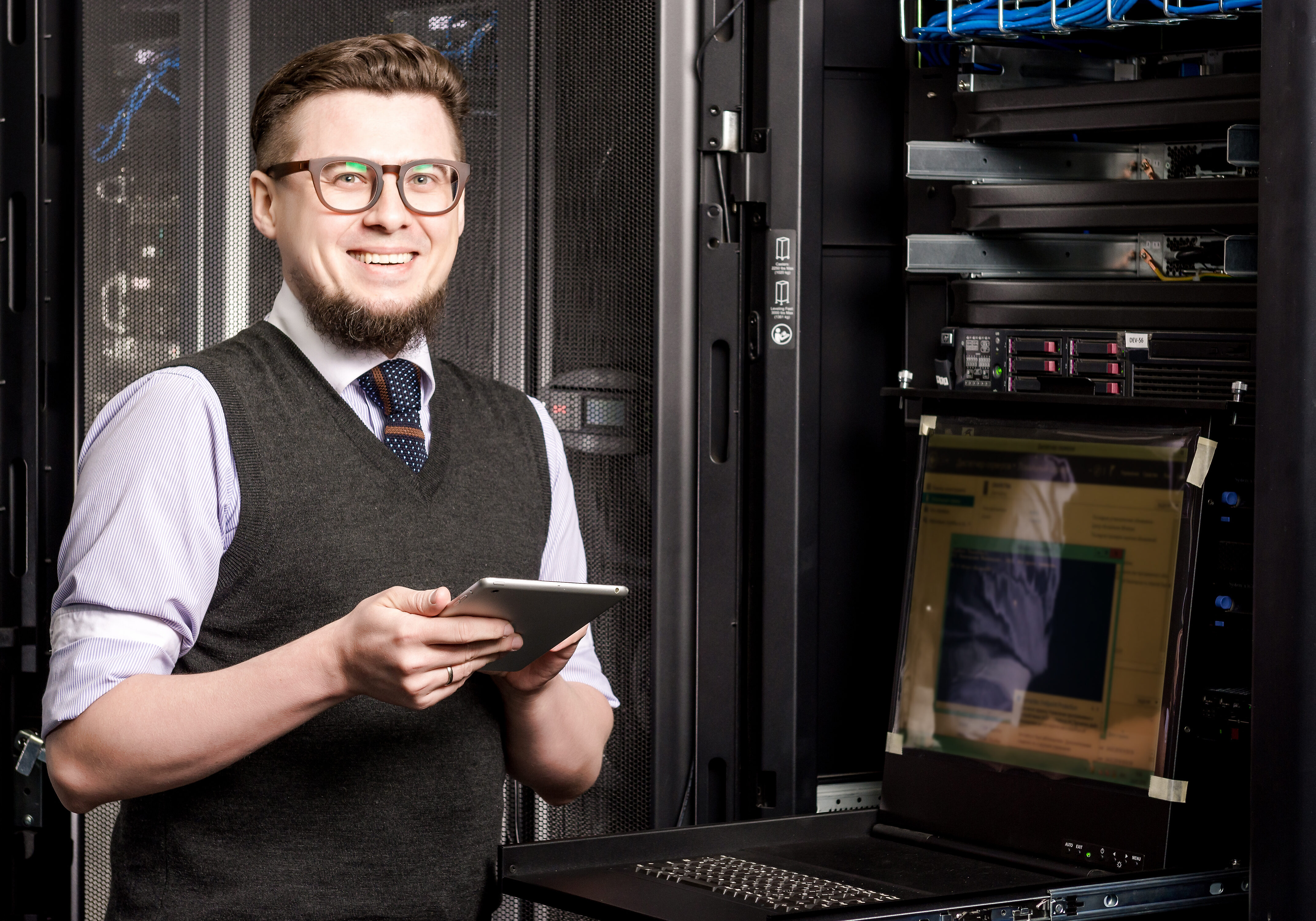 Young engineer wearing glasses in a datacenter